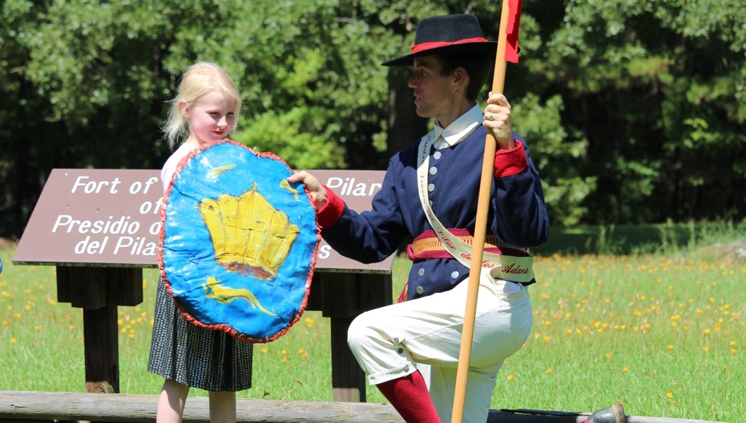 A young visitor with a reenactor in period clothing